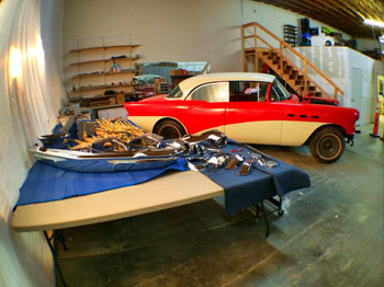 View of my 1956 Buick Special with chrome and stainless steel trim next to it on a table